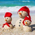 Beach. Snowmen family at sea beach in santa hats. New years and